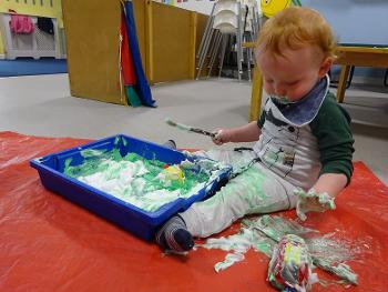 Son of key worker playing with paint at Abbey Nursery