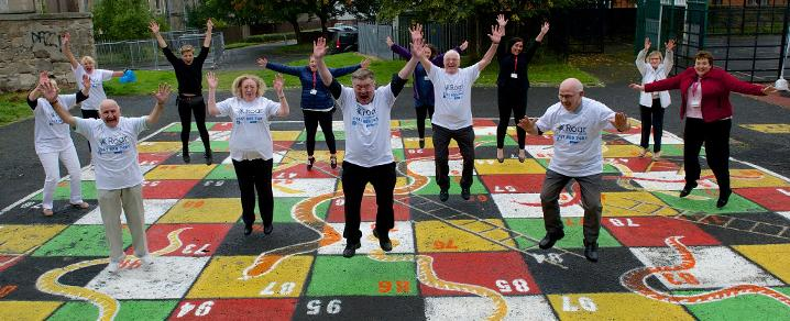 Reaching Older Adults in Renfrewshire (ROAR) and Renfrewshire Council's unpaid work team celebrate the unveiling of the snakes and ladders game artwork