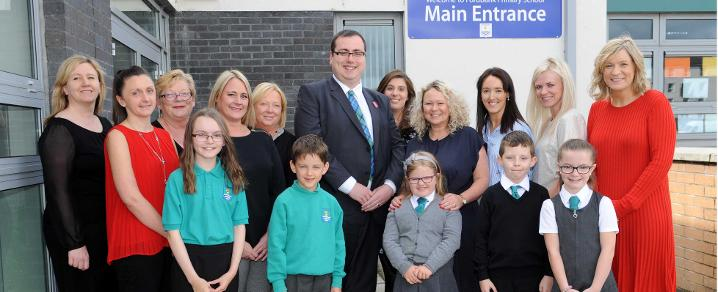 Teachers, classroom assistants and pupils from Fordbank Primary School celebrate positive inspection results.