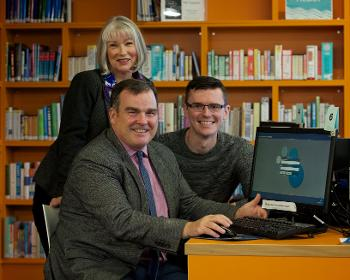 Council Leader Iain Nicolson with Digiteer Maggie McAlistair and Advice Works adviser Kevin Campbell